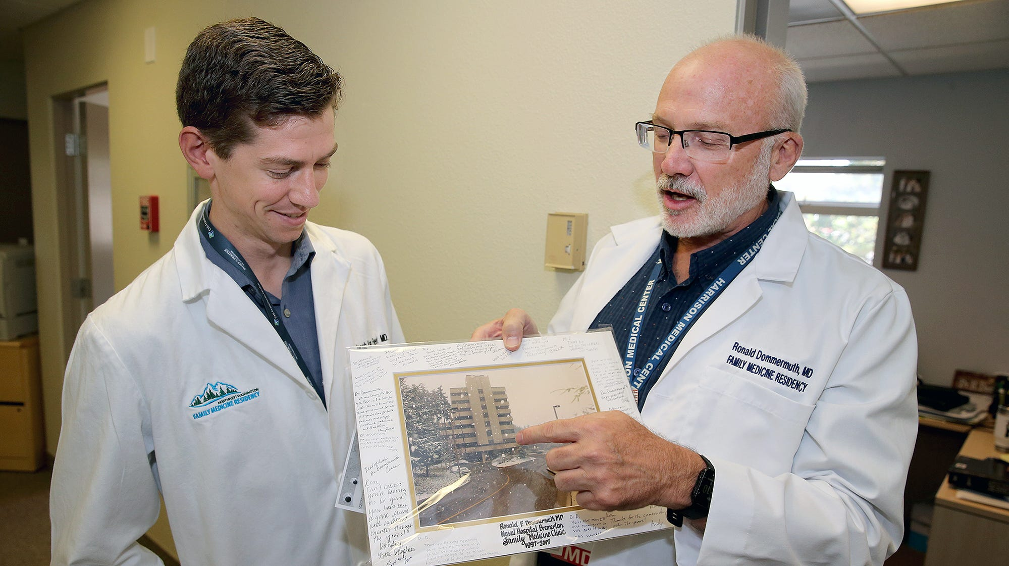 Harrison's residency program got underway this summer. Resident MD Jacob Van Fleet, left, who was born at the Naval Hospital in Bremerton, by doctor Ronald Dommermuth, right, who is now one of his instructors. Dommermuth is holding an old photo of Naval Hospital Bremerton.