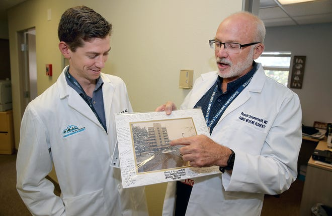 Harrison's residency program got underway this summer. Resident Jacob Van Fleet, left, was born at the Naval Hospital in Bremerton and was delivered by doctor Ronald Dommermuth, right, who is now one of his instructors. Dommermuth is holding an old photo of Naval Hospital Bremerton.