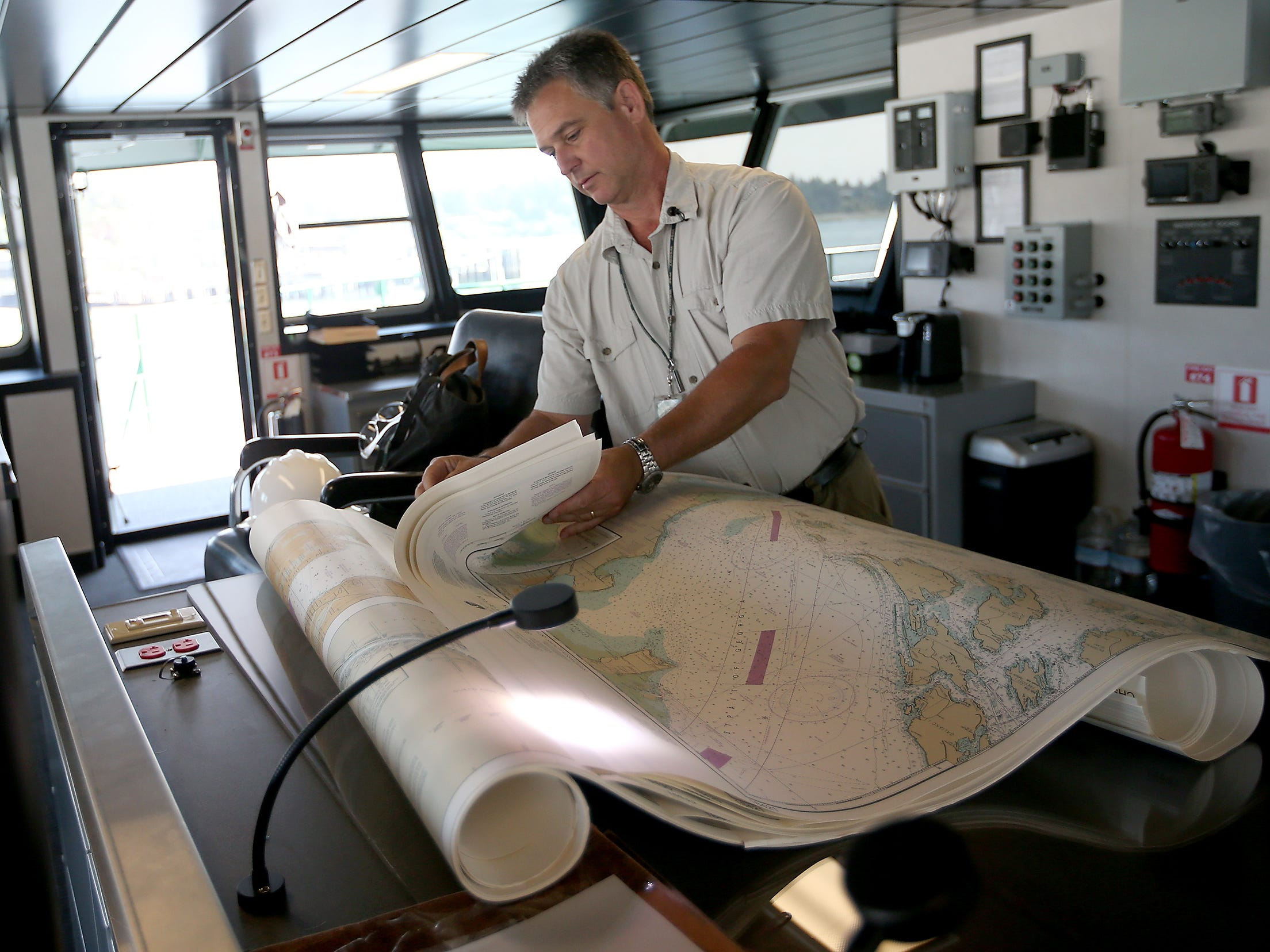 Capt. Greg Sugden sorts through navigational charts as he gets the bridge of the Washington State Ferry Suquamish ready for its upcoming sea trials, while docked at the Eagle Harbor Maintenance Facility on Thursday, August 9, 2018.
