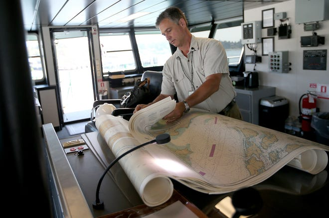 Capt. Greg Sugden sorts through navigational charts as he gets the bridge of the Washington State Ferry Suquamish ready for its upcoming sea trials. The Suquamish, WSF's newest boat and the fourth of the Olympic class of vessels, is docked at the Eagle Harbor Maintenance Facility on Bainbridge Island.