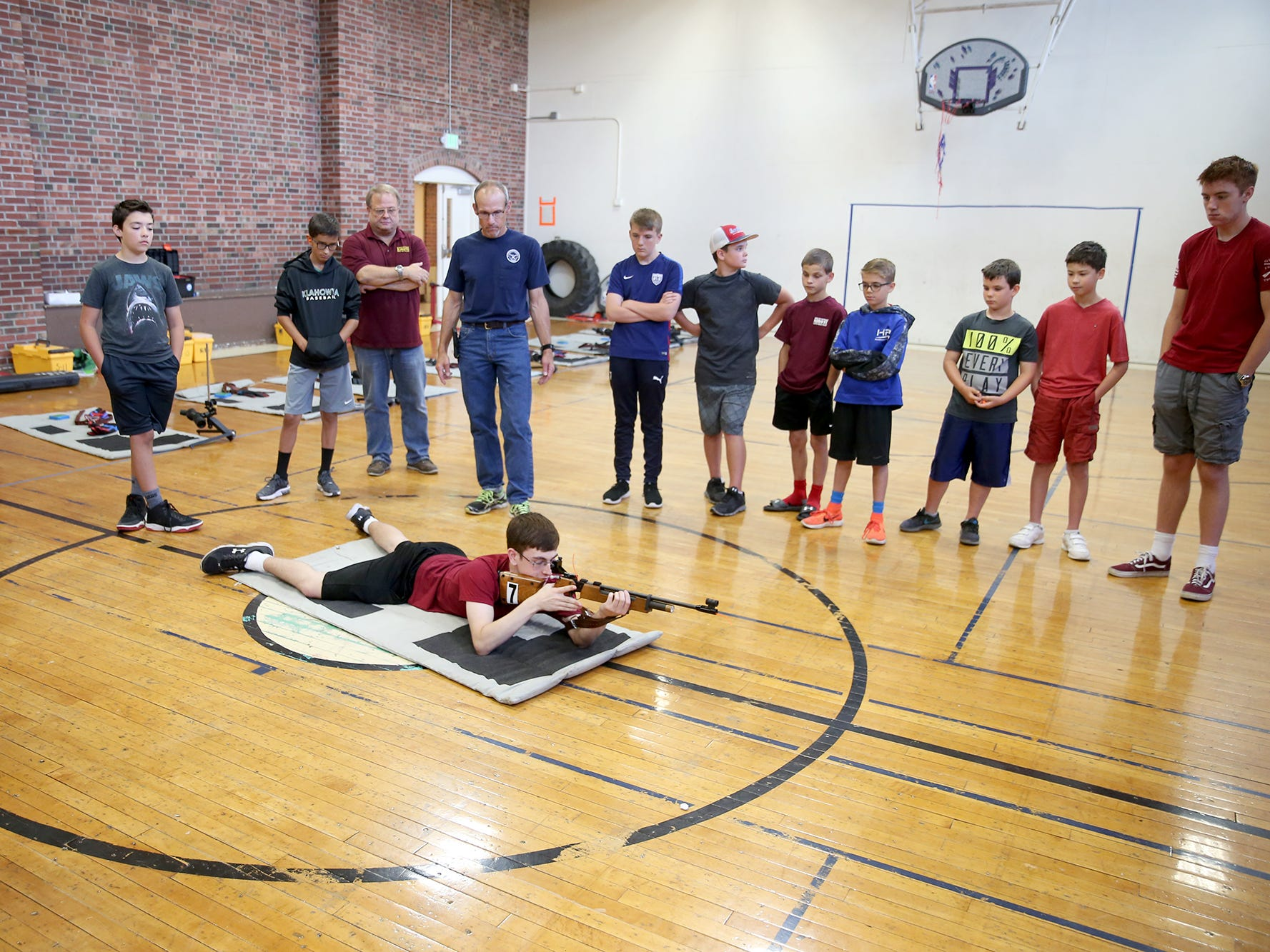 Camp instructor aide Sean Webb, 16, shows students the correct prone shooting position at the South Kitsap High School NJROTC Wolf Battalion Rifle Camp runs from August 8-10, at the National Guard Armory in Port Orchard.The camp teaches rifle safety, and shooting technics.