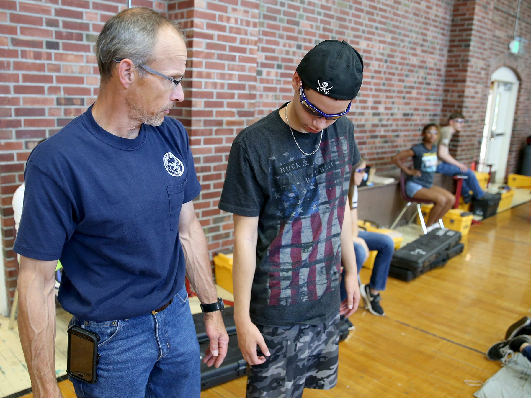Rifle instructor Jeff Phillips compares the leg length of student Braden Brown, 15, to make sure he has the right sized air rifle at the South Kitsap High School NJROTC Wolf Battalion Rifle Camp runs from August 8-10, at the National Guard Armory in Port Orchard.The camp teaches rifle safety, and shooting technics.