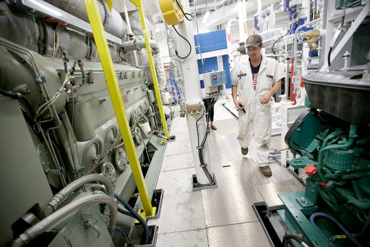 Nate Ratcliff, a staff chief engineer with the Washington State Ferries, moves through one of the engine rooms while working aboard the Suquamish at the Eagle Harbor Maintenance Facility on Bainbridge Island.