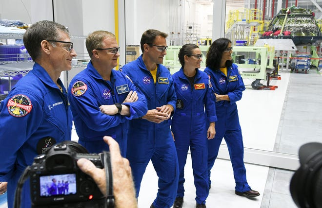 Astronauts Chris Ferguson, Eric Boe, Josh Cassada, Nicole Mann and Suni Williams stand for pictures in the Boeing Starliner manufacturing facility at Kennedy Space Center.