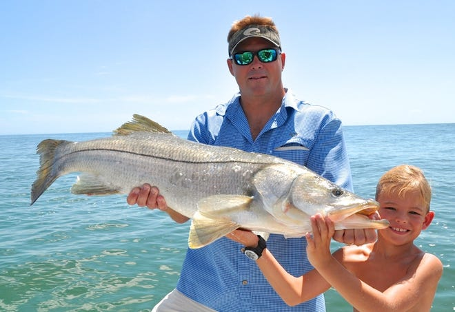 Shannon O'Quinn gets help from his son Austin in showing the 40-inch trophy snook caught and released while fishing with Capt. Glyn Austin who will give a free clinic in Melbourne on Tuesday Aug. 14 on the ways to fish the upcoming fall mullet run.
