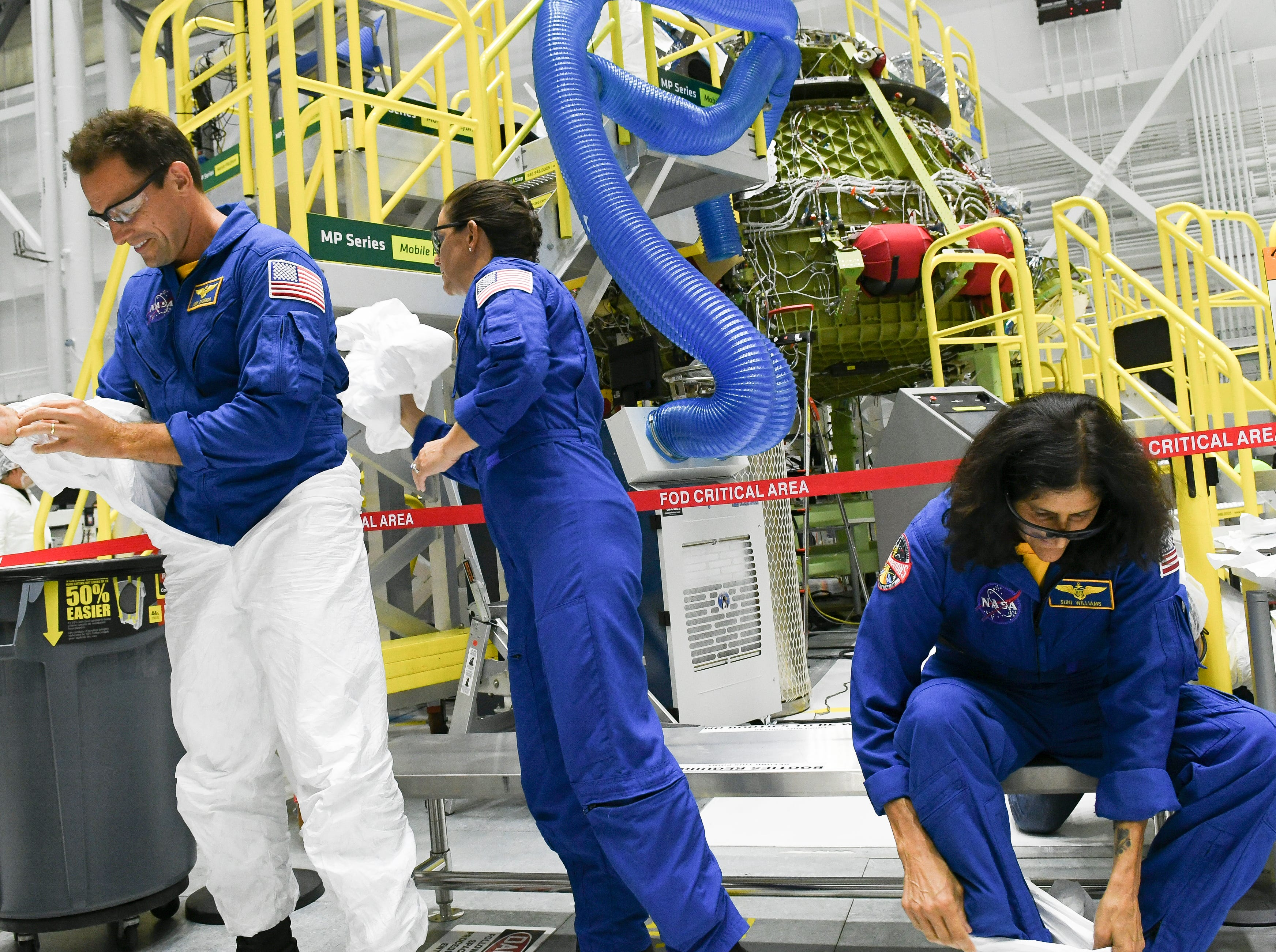 Astronauts Josh Cassada, Nicole Mann and Suni Williams climb out of their protective suits after getting a close look at the Starliner crew test vehicle in the Boeing  manufacturing facility at Kennedy Space Center.