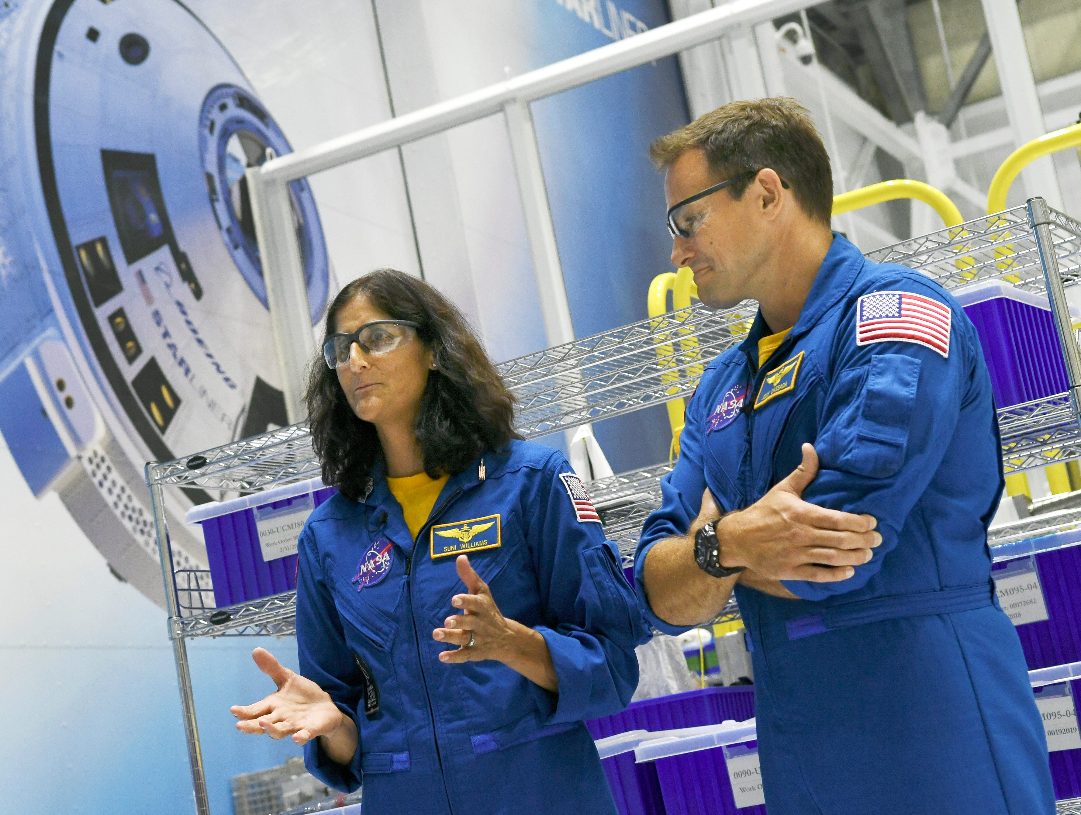 Astronauts Suni Williams and Josh Cassada stand in front of one of the Starliner crew vehicles in the Boeing manufacturing facility at Kennedy Space Center.