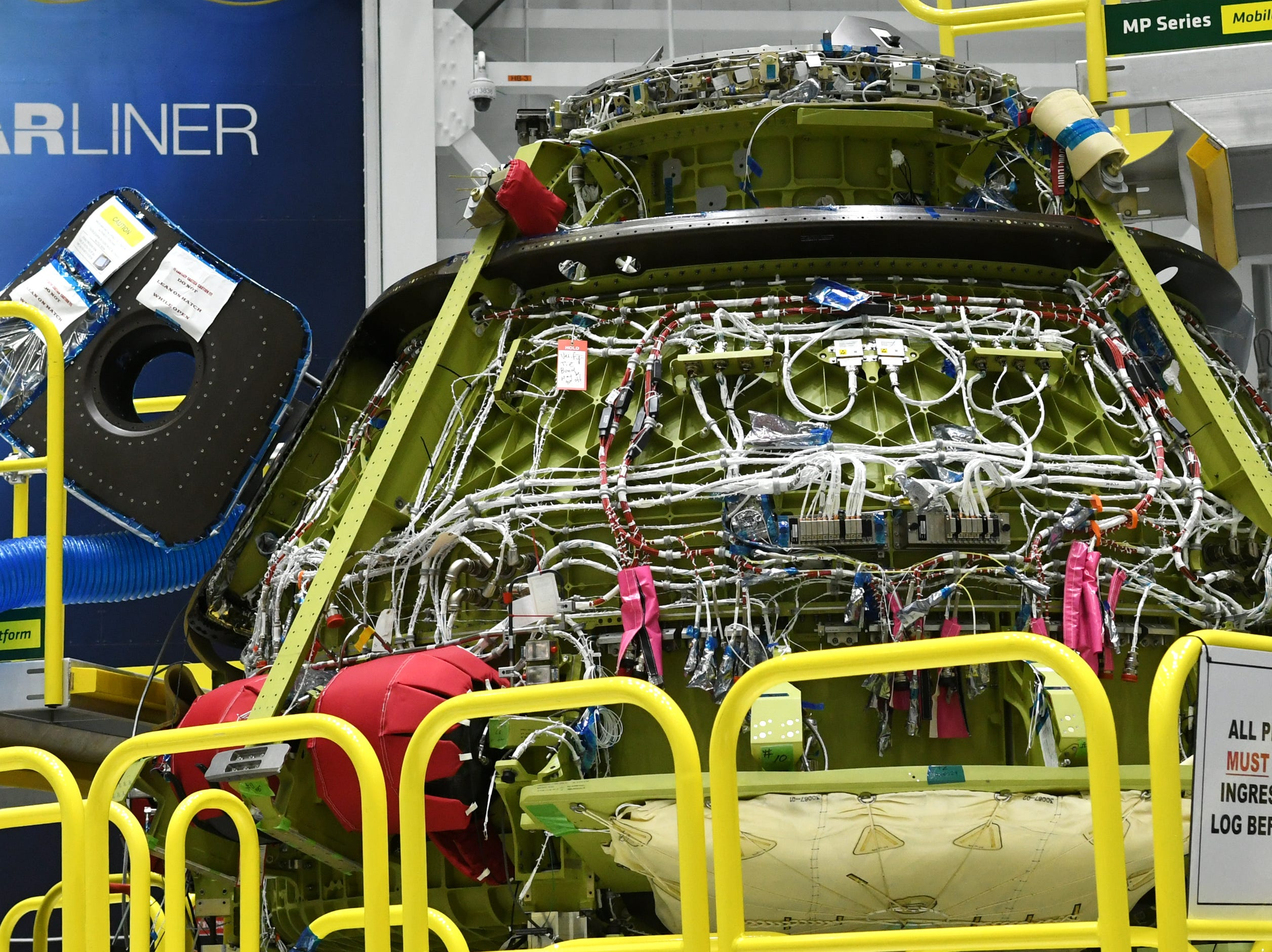 The Starliner crew test vehicle sits on its stand in the Boeing manufacturing facility at Kennedy Space Center.