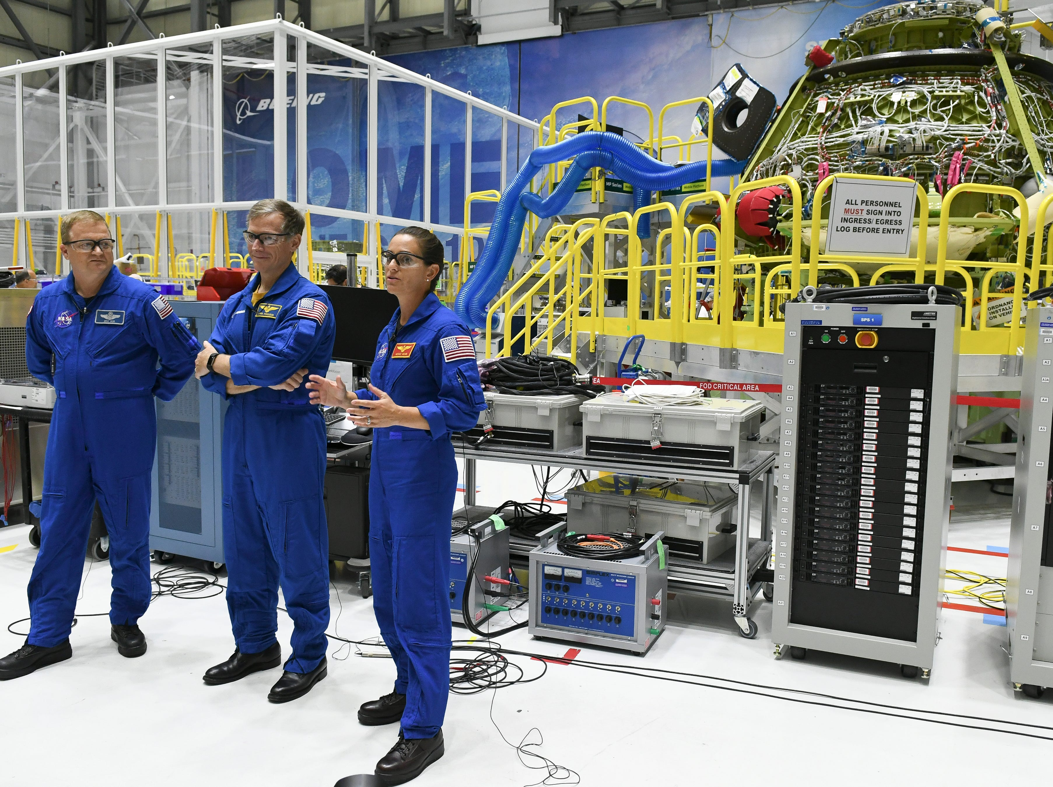 Astronauts Eric Boe, Chris Ferguson and Nicole Mann stand in front of the Starliner crew test vehicle in the Boeing  manufacturing facility at Kennedy Space Center.