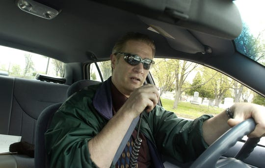 Chittenden County Sheriff Kevin McLaughlin talks on his radio while driving through Burlington in May 2003.