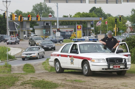 Michael Major, then-Sergeant of the Chittenden County Sheriff's Department, monitors traffic near the Interstate overpass construction site on Williston Road in South Burlington in June 2003.