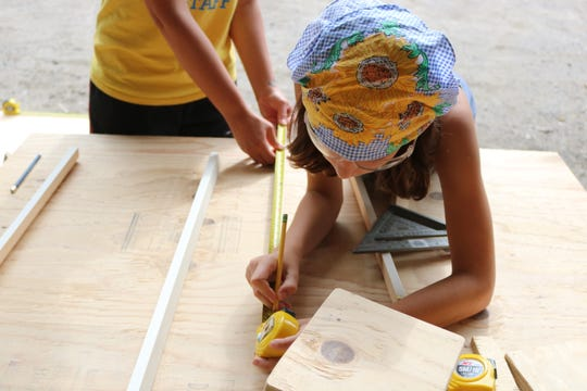 Anna Town, 11, who loves math, designed and was measuring wood for a folding chair design at Rosie's Girls Build Camp on Aug. 9, 2019.