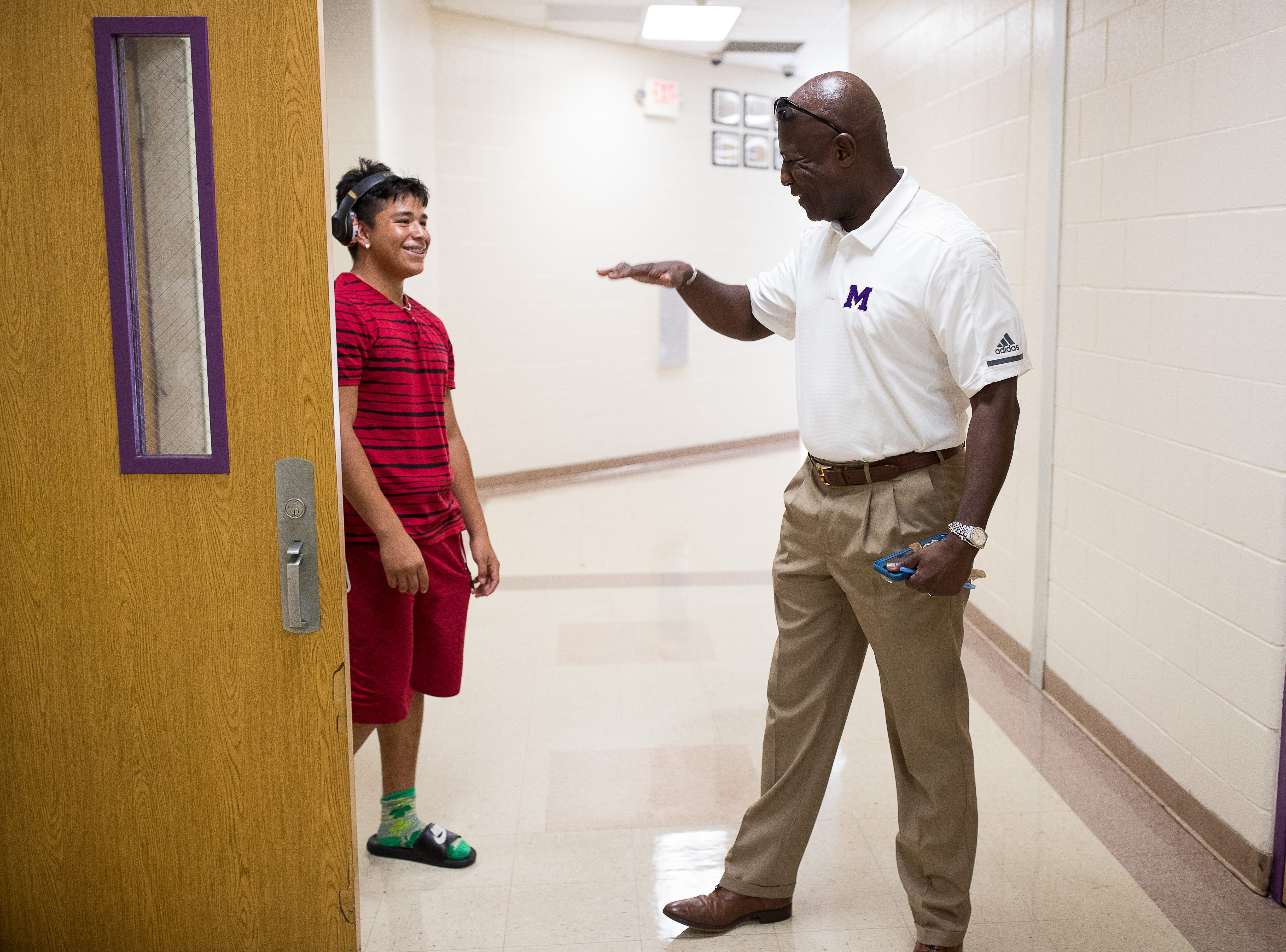 Miller High school's new principal Bruce Wilson talks to a student in the hallway on his way to a meeting before the start of the new school year on Thursday, Aug. 9, 2018.