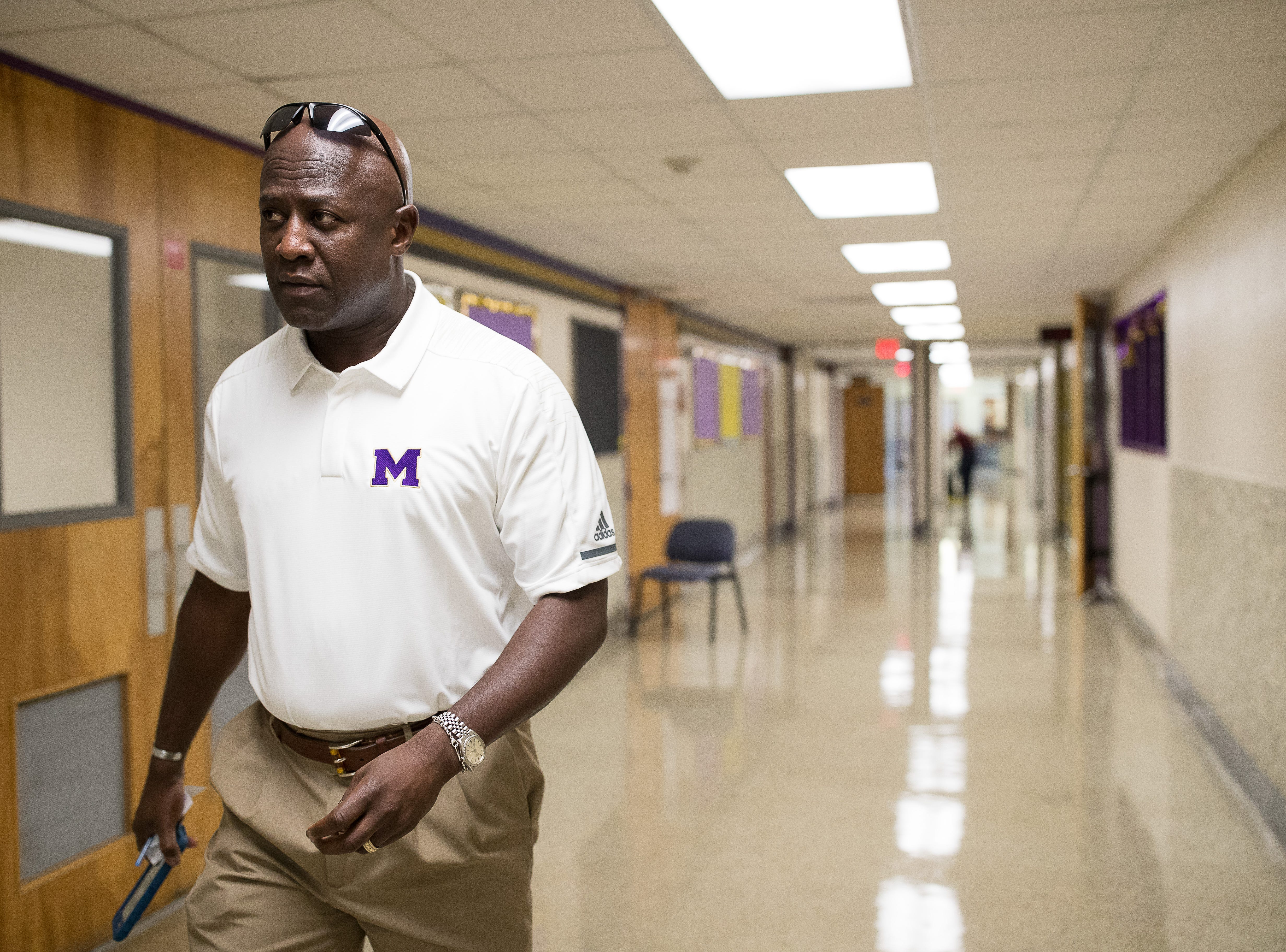 Miller High school's new principal Bruce Wilson walks down the hallway of his new school before the start of the new year on Thursday, Aug. 9, 2018.