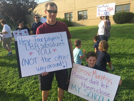 Brian Larkin (left) and his son Kevin hold up their signs at the rally at Teddy Bear Academy on Wednesday evening. They hope the academy does not close down.