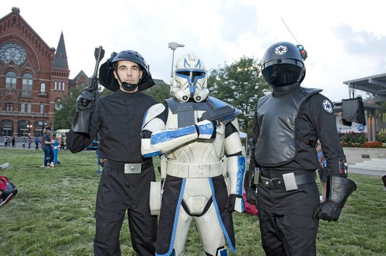 "A Star Wars costume contest preceded the free showing of ""Star Wars: The Last Jedi"" in Washington Park on Wednesday. Brent Hawkins of Blue Ash, Steve Langenbrunner of Mason and Nick Fox of Middletown were at the park representing the Imperial Forces of the Empire."