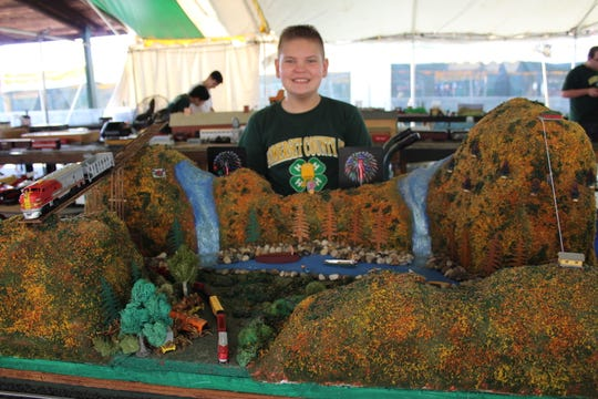 Jeff Bate, a 3rd year Trainmaster, stands by his scenery display at the 4-H Fair