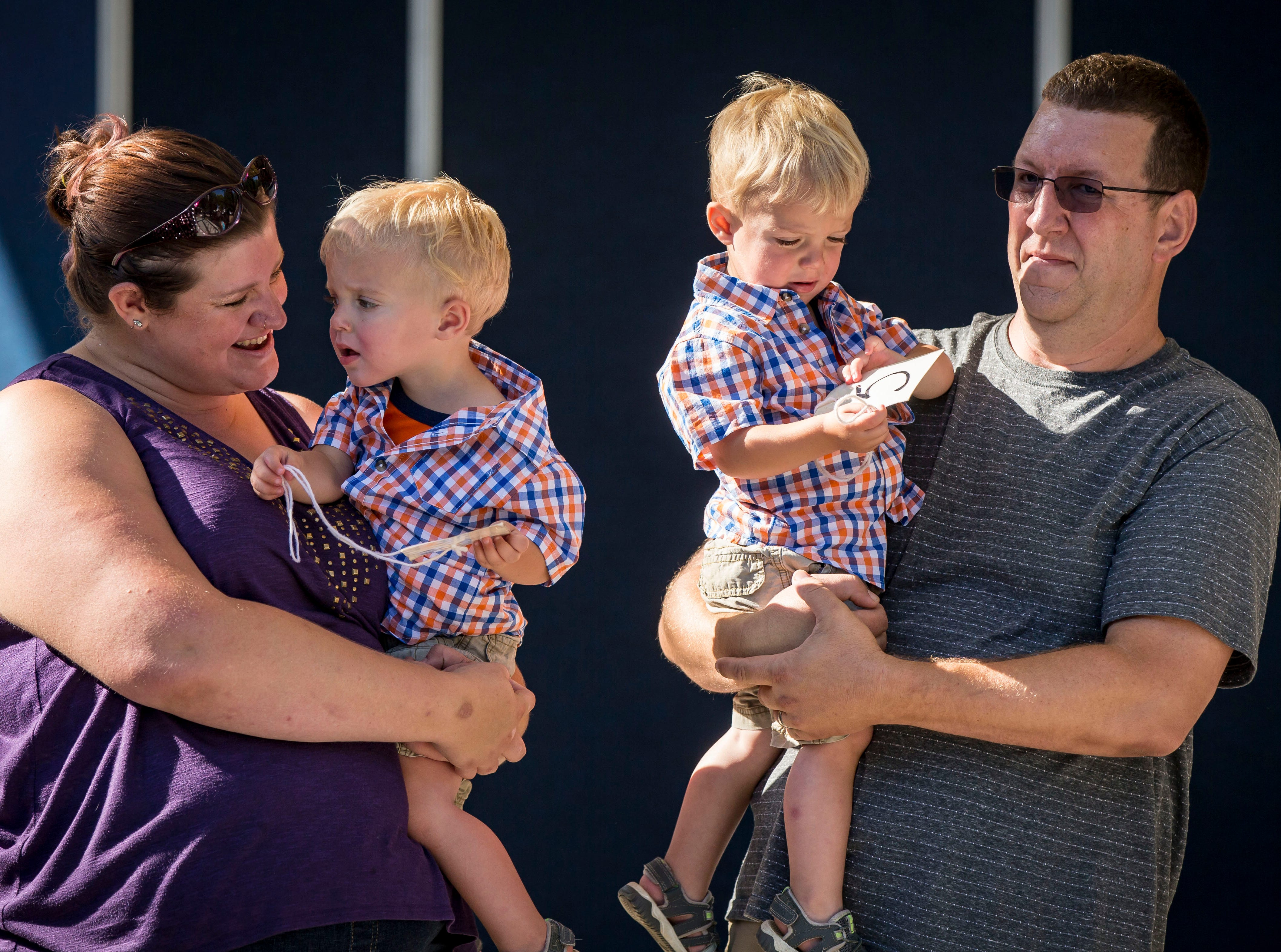 Benjamin,left, and Luke Hildal of Jewell wait with their parents Katie and Drew in the two-year-old category during the Twins, Triplets and More Contest on the Anne and Bill Riley Stage at the 2018 Iowa State Fair in Des Moines Thursday, Aug. 9, 2018.