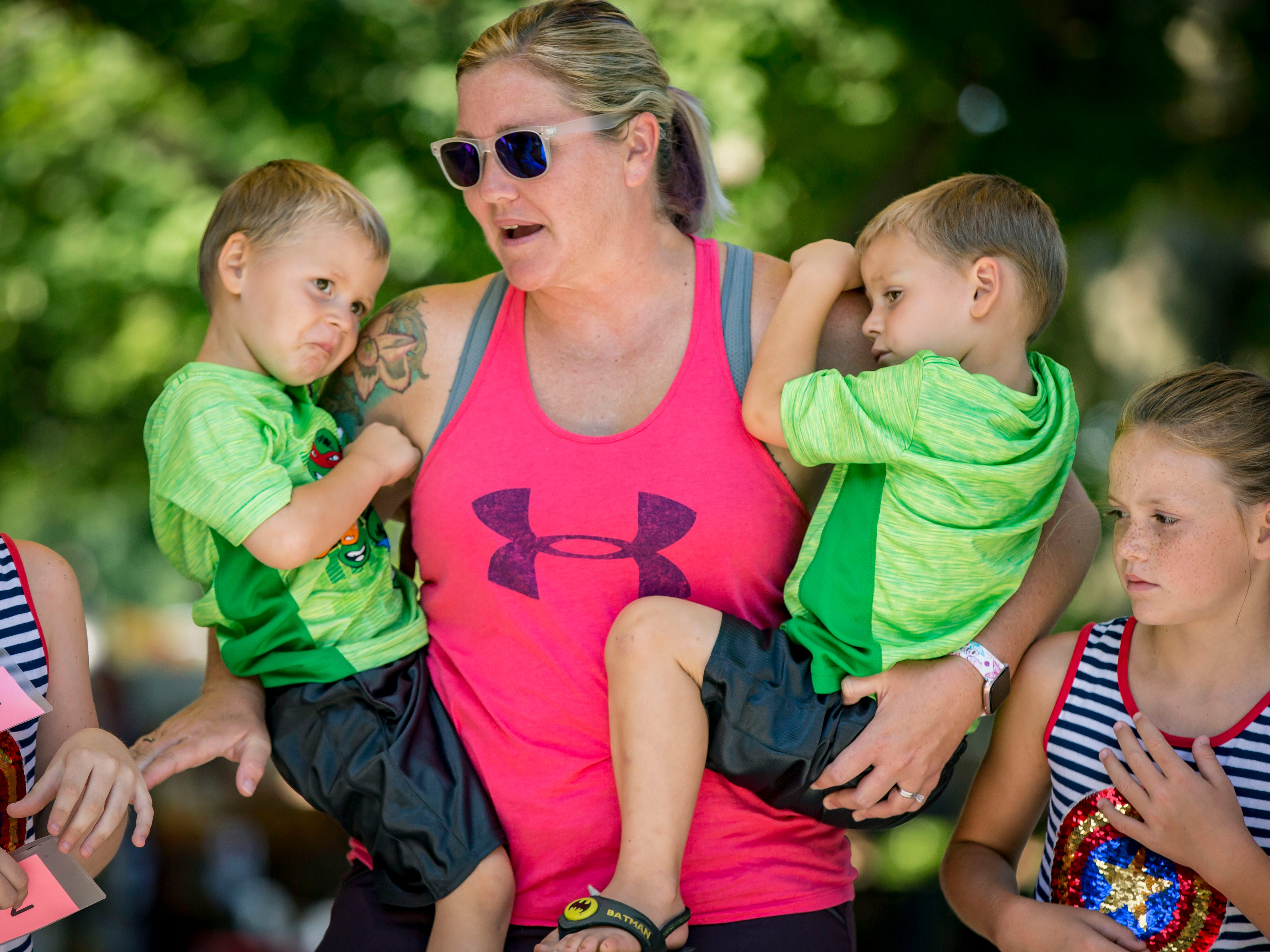 Archer, left, and Cash Janssen of New Virginia are held by their mother Amy during the Twins, Triplets and More Contest on the Anne and Bill Riley Stage at the 2018 Iowa State Fair in Des Moines Thursday, Aug. 9, 2018.