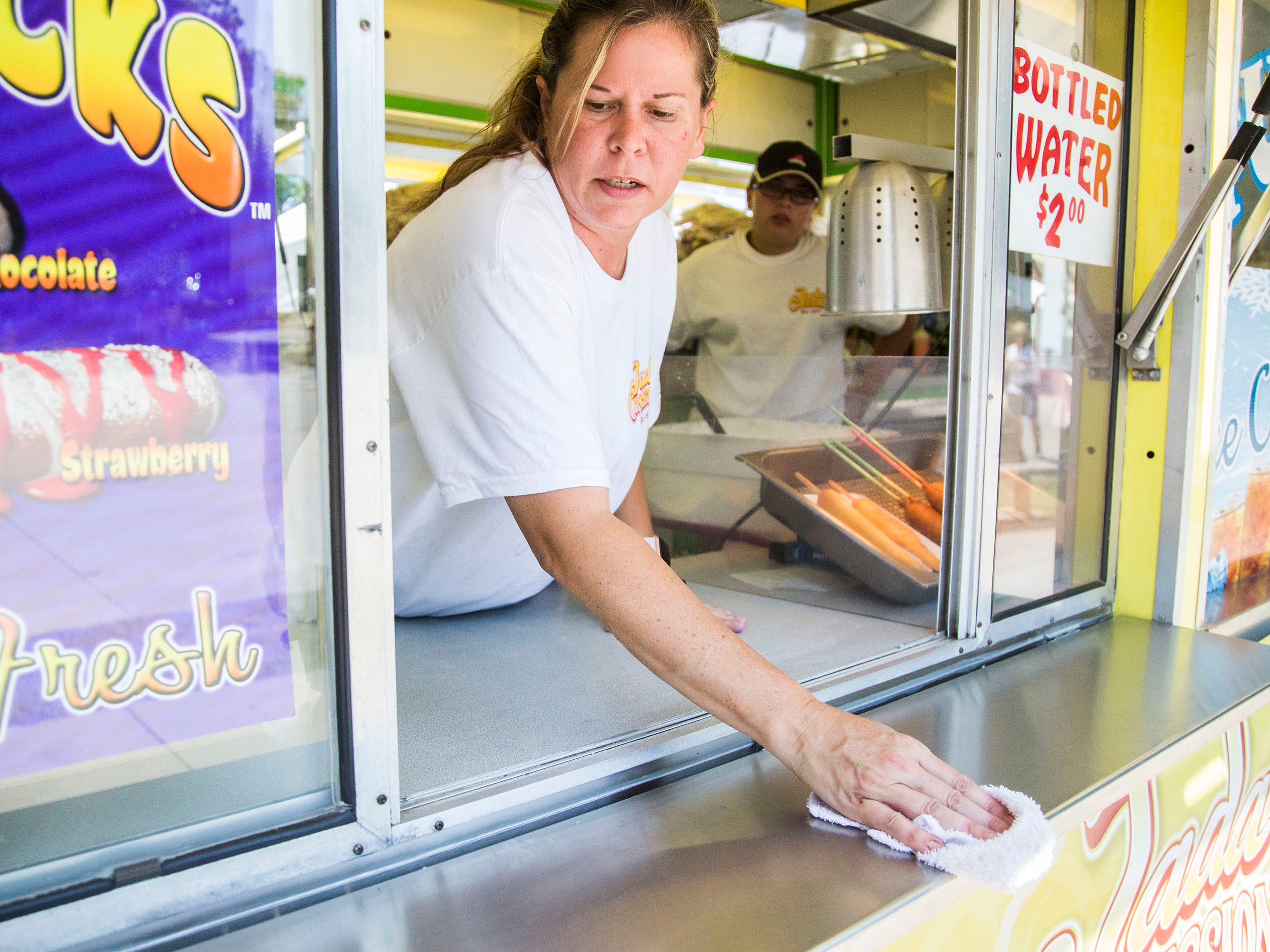 During a lull in activity, Jada Blewer, owner of Jada Concessions, wipes a counter in her funnel cake concession stand on Thursday, Aug. 9, 2018, at the Iowa State Fair.