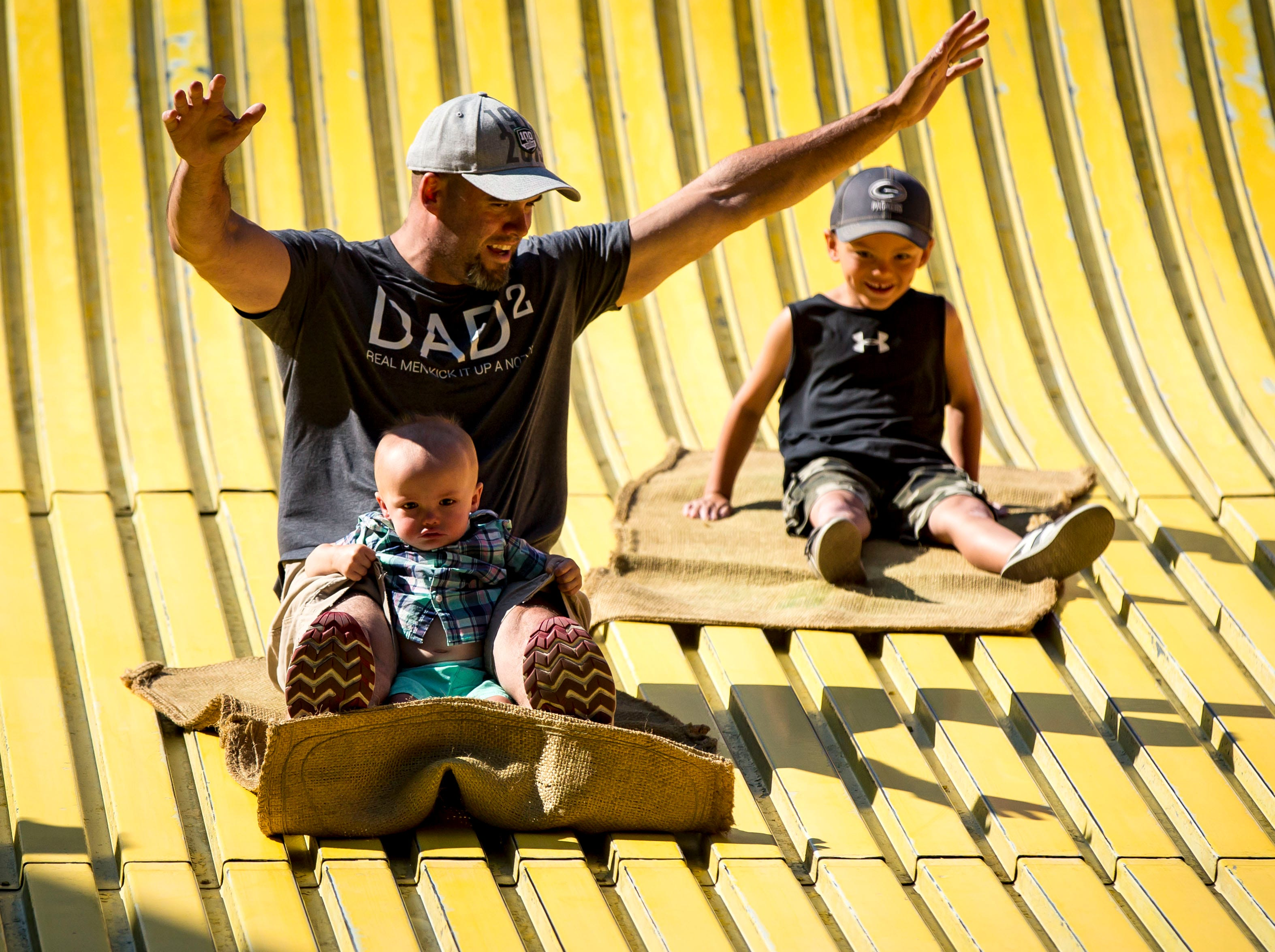 Chad Lowe of Des Moines holds his son Camdyn, age 1, while racing his son, Cayson, 6, right, on the giant slide at the 2018 Iowa State Fair in Des Moines Thursday, Aug. 9, 2018.