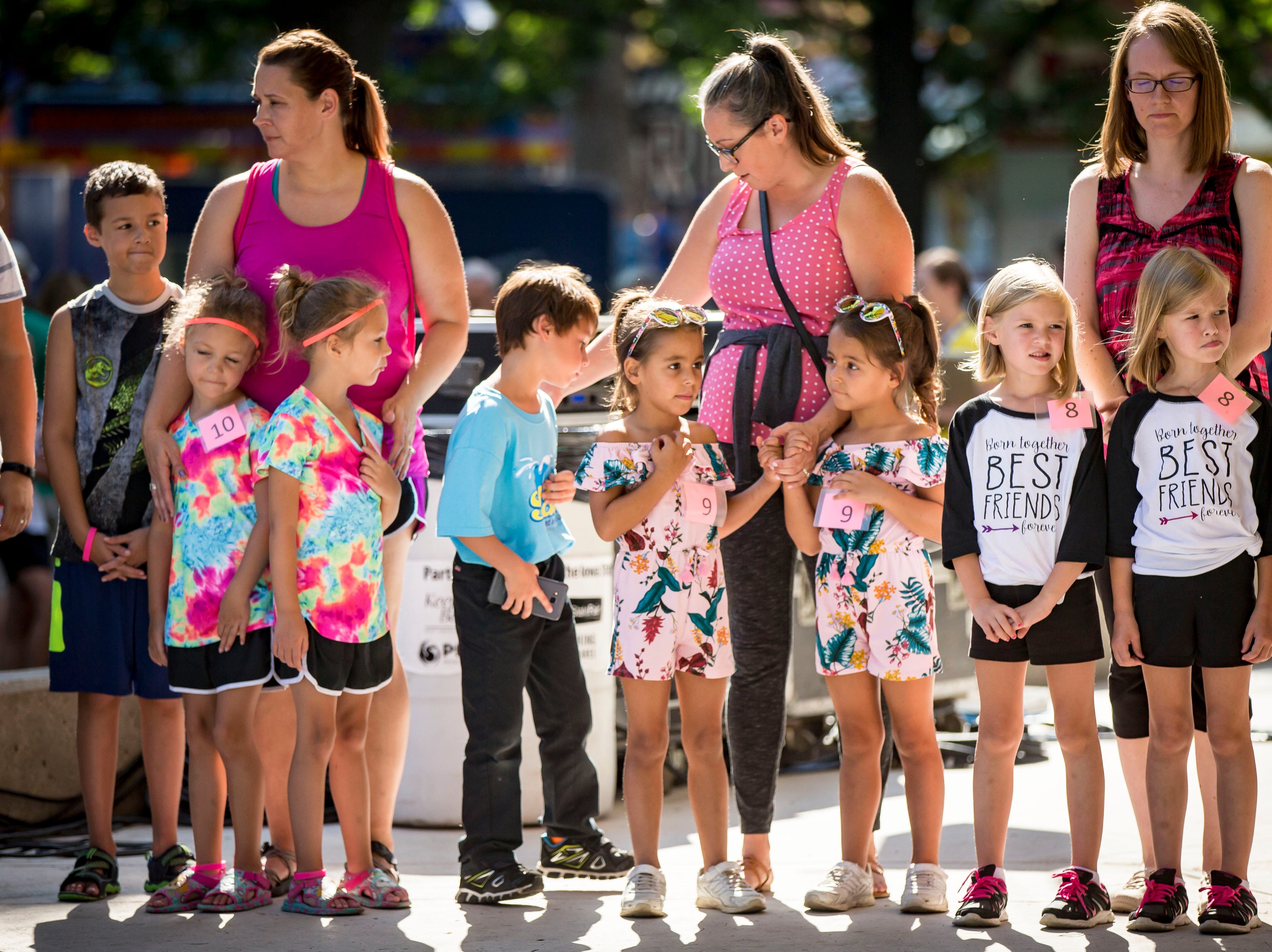 Five-year-olds wait to compete in the most alike category during the Twins, Triplets and More Contest on the Anne and Bill Riley Stage at the 2018 Iowa State Fair in Des Moines Thursday, Aug. 9, 2018.