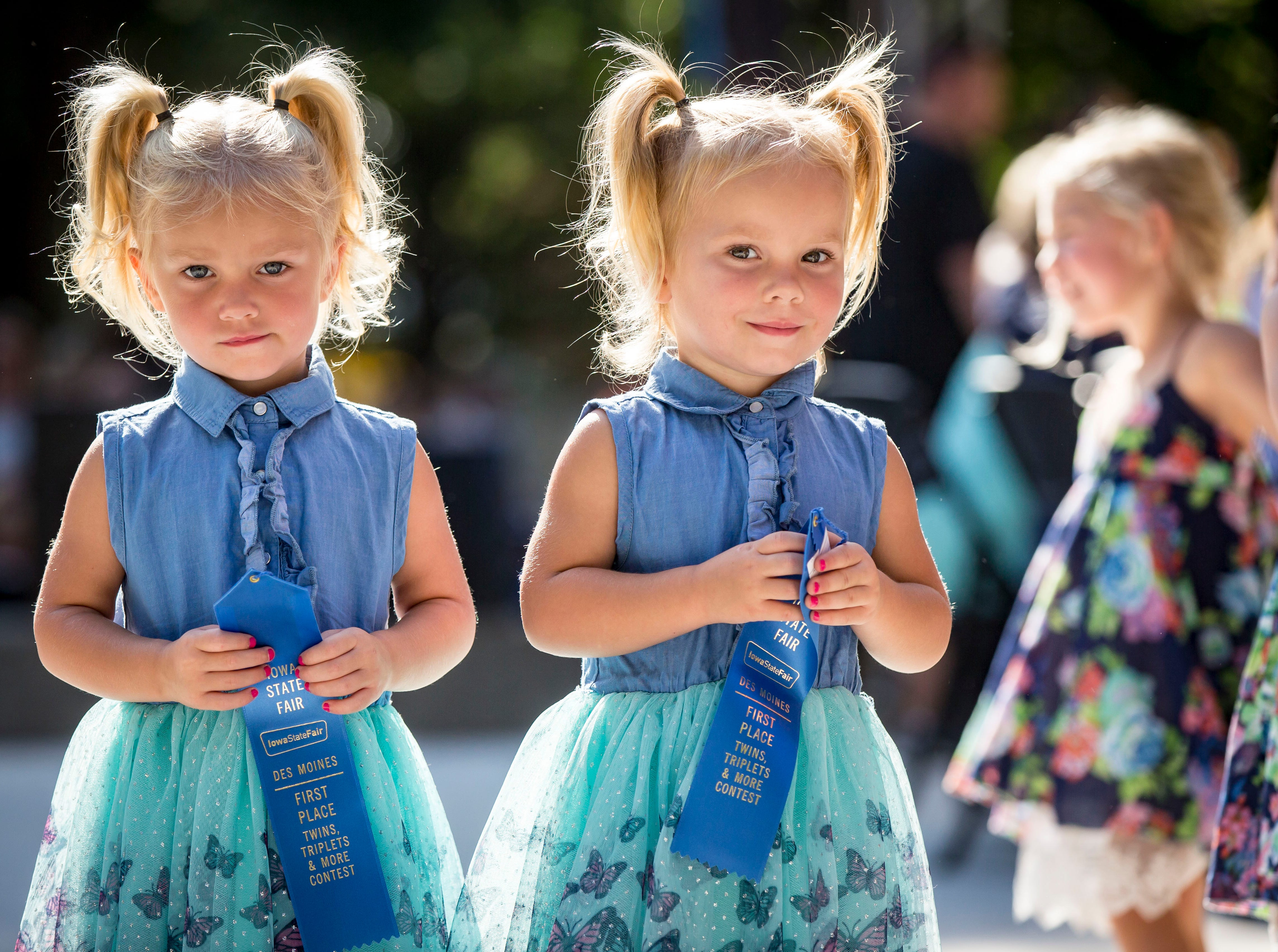 Three-year-old most alike blue ribbon winners Ellie, left, and Ava Goodrich of Ankeny during the Twins, Triplets and More Contest on the Anne and Bill Riley Stage at the 2018 Iowa State Fair in Des Moines Thursday, Aug. 9, 2018.