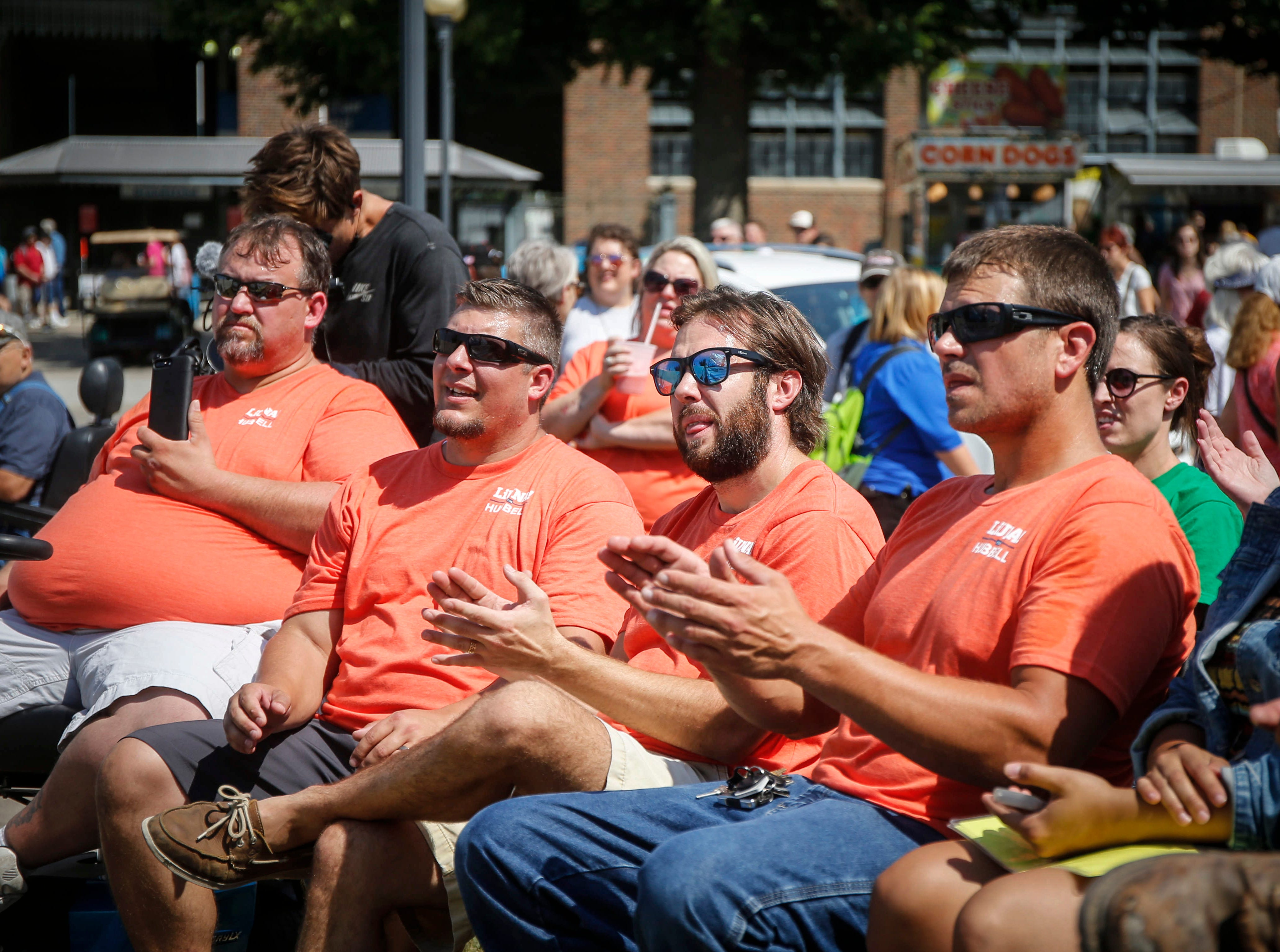 Union labor workers applaud as they hear from Democrat Abby Finkenauer at the Political Soapbox during the Iowa State Fair in Des Moine.