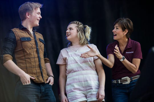 Caleb Lee Hutchinson, American Idol contestant, Maddie Poppe, winner of season 16 of American Idol and Iowa native, stands on stage with Iowa Governor Kim Reynolds during the opening ceremonies for the Iowa State Fair on Thursday, August 9, 2018, in Des Moines.