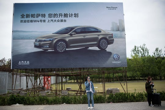 People stand under a billboard of a Volkswagen car commercial on the eve of the Beijing Auto Show in Beijing on April 24, 2018.