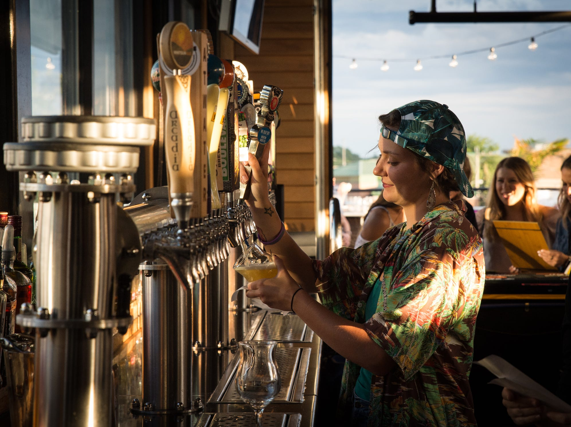 Sarah Heuninck of Detroit pours drafts on the third floor terrace of HopCat in Royal Oak on Friday, July 20, 2018.