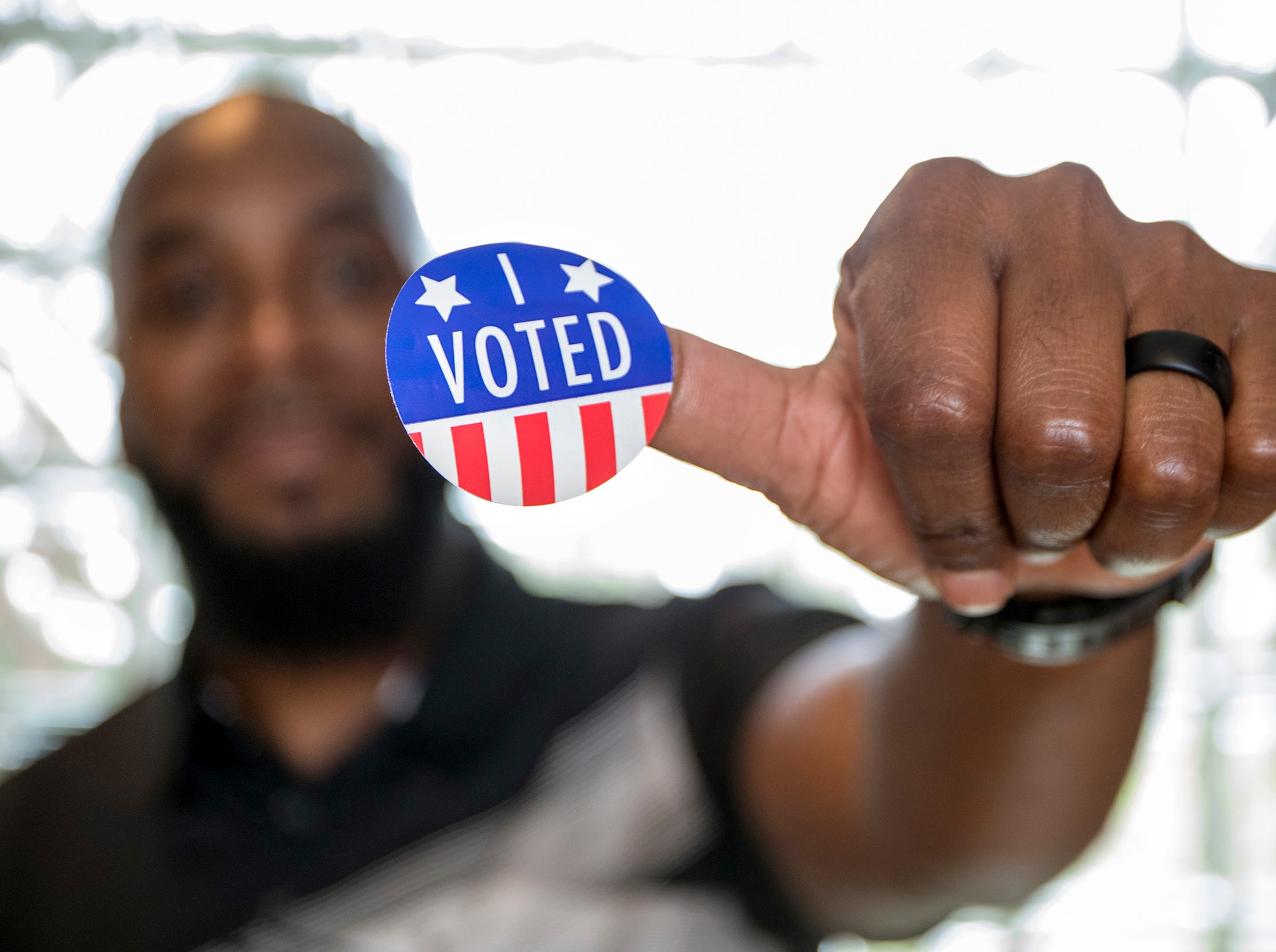 Sam Benford, 46 of Mt. Clemens holds up his sticker after voting at the Wilson Gymnasium polling location in Mt. Clemens, Mich., Tuesday, August 7, 2018.