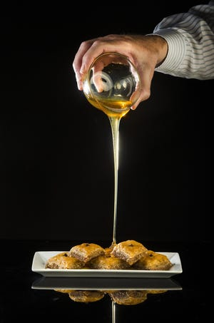 Honey is poured over baklava, a traditional greek dessert with honey and nuts, in the Post-Dispatch studio Wednesday, June 27, 2018. (Ryan Michalesko/St. Louis Post-Dispatch/TNS)
