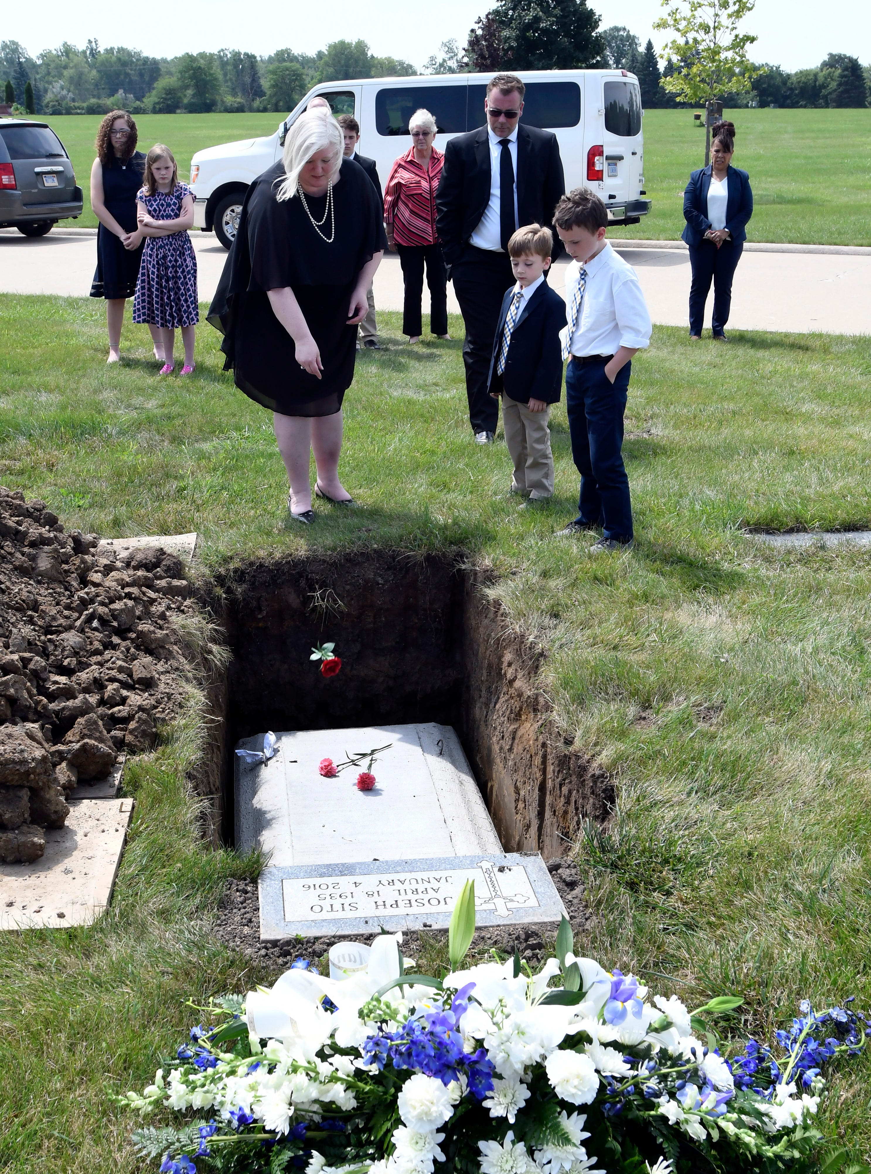 Tiffany Brocker of Detroit, left, is surrounded by family as she tosses a flower onto the casket of Gordon King.