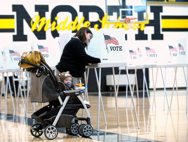 Sixteen-month-old Gabriel Boivin keeps a watchful eye as his mother, Suzanna Smith, both of Macomb Twp., votes at Precinct 2 as Macomb Twp. residents vote at Precincts 2 and 31 inside L'Anse Creuse Middle School as precinct workers facilitate their ballot processing, Tuesday afternoon, November 8, 2016.