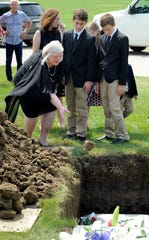 Tiffany Brocker of Detroit, left, is surrounded by family as she tosses dirt onto the casket of Gordon King.