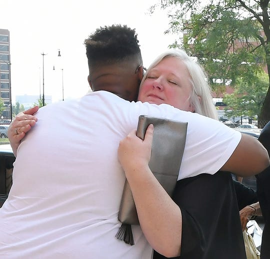 Tiffany Brocker, right, is hugged by Jelani Shakoor, who used to be homeless and had also known Gordon King.