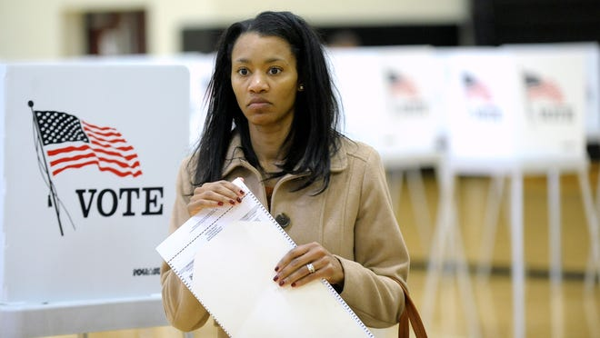 Chawanne Burns, 38, of Macomb Twp., prepares to cast her ballot at L'Anse Creuse Middle School as precinct workers facilitate their ballot processing, Tuesday afternoon, November 8, 2016.