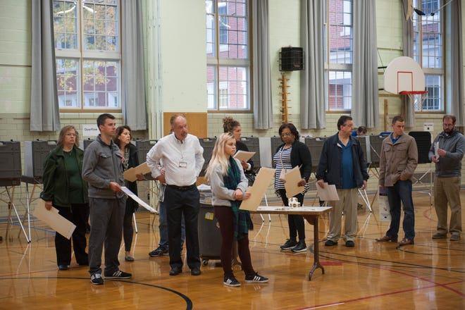 Having filled out their ballots, Grosse Pointe Woods residents wait in line to feed them into the tabulating machine at the Precinct 5 voting station in the gymnasium inside Montieth Elementary School in Grosse Pointe Woods were there was a strong early turnout of voters casting ballots in the 2016 Presidential Election on Tuesday, November 8, 2016.