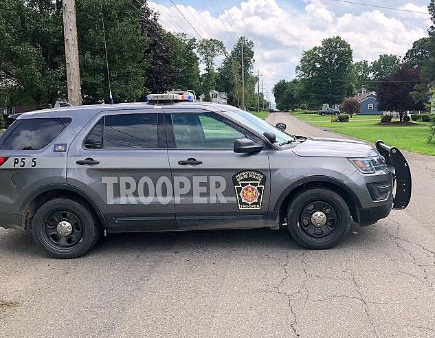 A Pennsylvania state police vehicle sits near the scene of a standoff Wednesday in Athens Township.