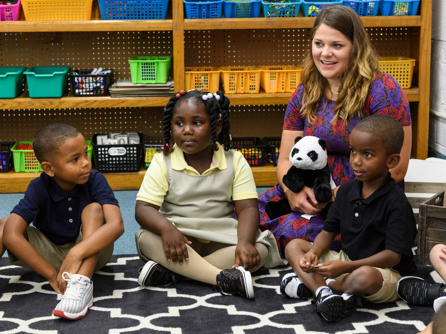 "Counselor Elizabeth Samelak, third from left, sits with kindergarten students in Brooke Havill's classroom on the first day of school at Dexter Elementary School in Evansville, Ind., Wednesday, Aug. 8, 2018. Samelak introduced a stuffed panda named Andy to the kindergarteners incase they needed extra comfort. ""It's his first day of school too and he is a little scared,"" she told them."