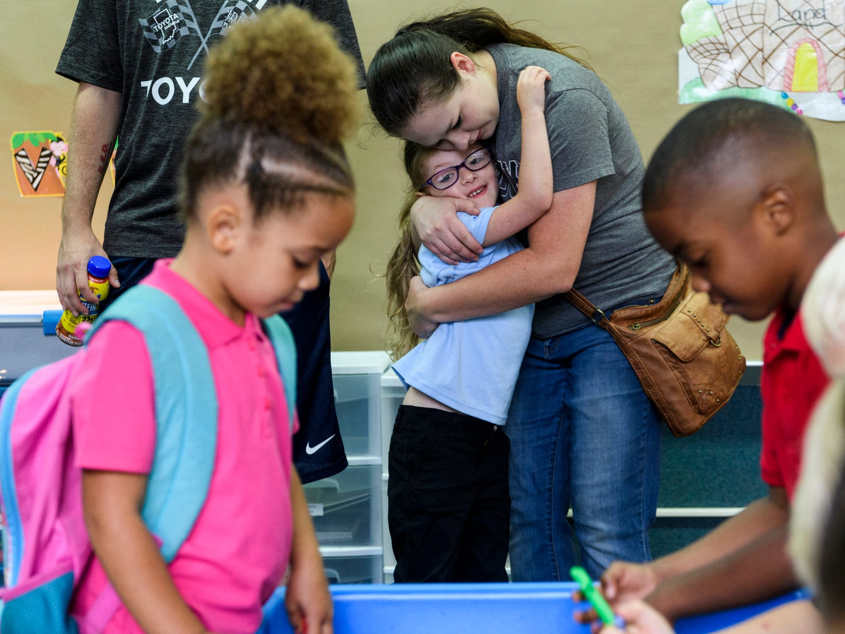 Eliza Ohning, center left, receives a hug from her mother Tyanna Frick, center right, before being left in her kindergarten classroom with teacher Lyndsey Schneider, not pictured, and her new classmates on the first day of school at Dexter Elementary School in Evansville, Ind., Wednesday, Aug. 8, 2018.
