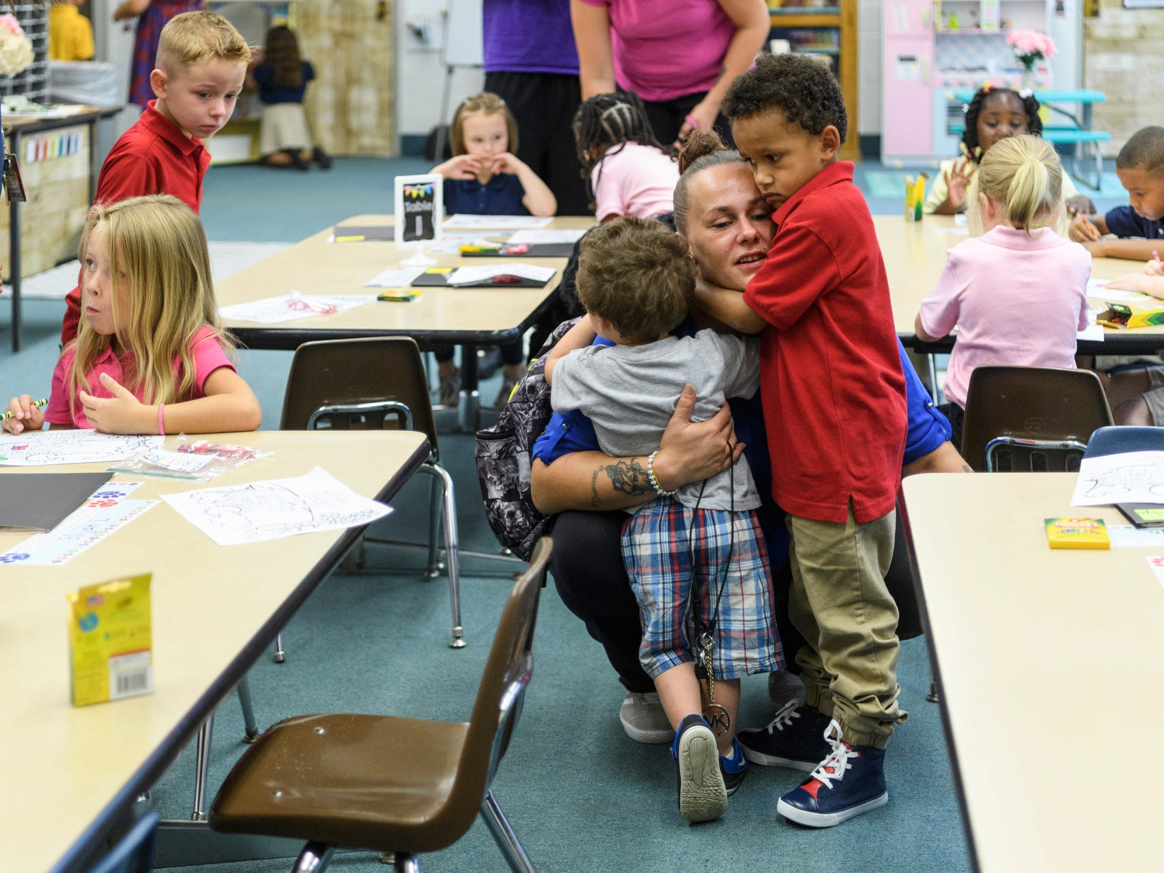 "Amanda Brune, center, hugs her two children Carter Brune, left, and Brayden Thomas, right, before leaving Brayden with kindergarten teacher Brooke Havill, not pictured, on the first day of school at Dexter Elementary School in Evansville, Ind., Wednesday, Aug. 8, 2018. ""He has been very excited for school so once he settles in he will be just fine,"" Brune said, as she left the classroom."