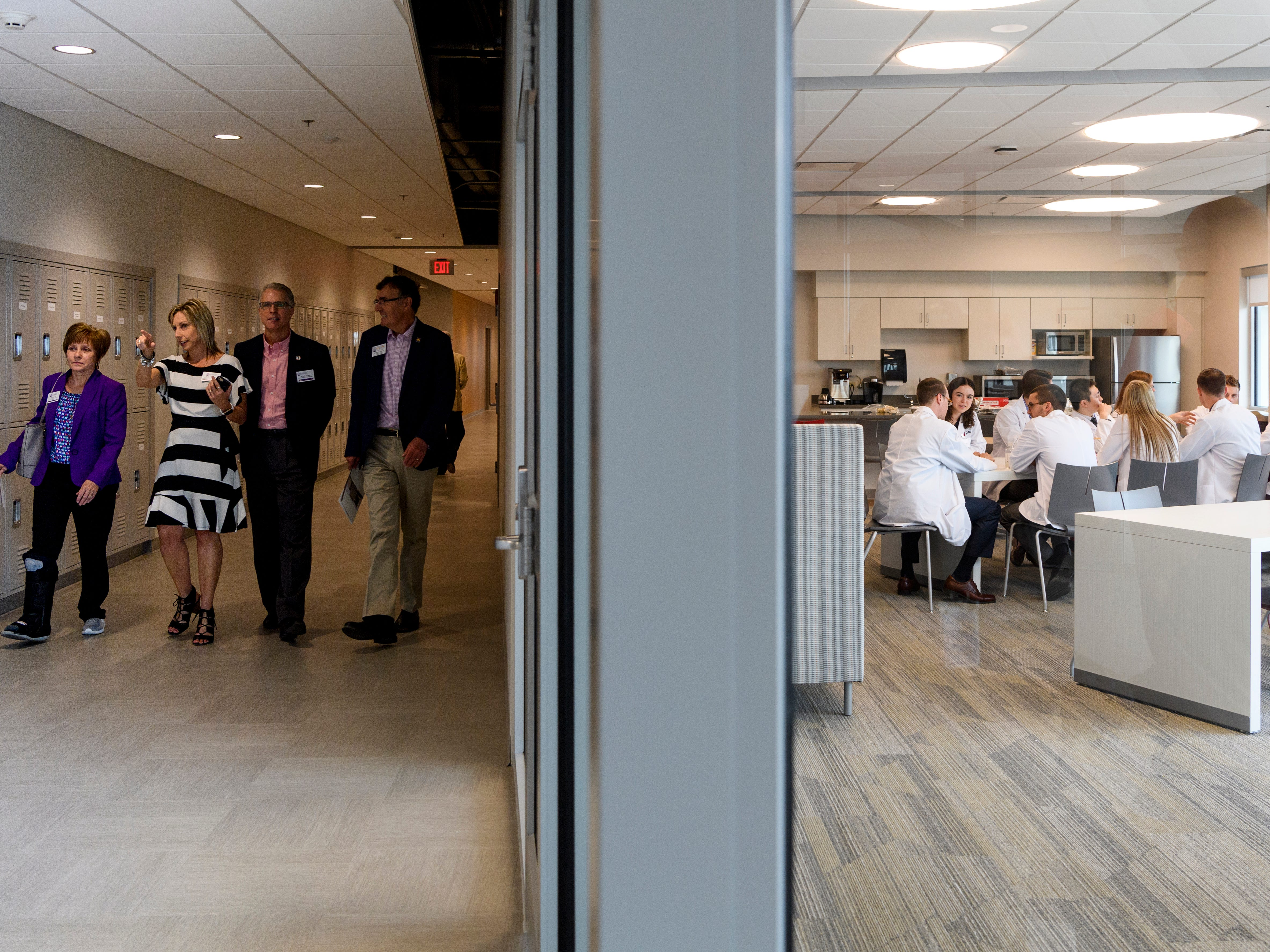 After the building dedication ceremony and ribbon cutting, community members tour the new Stone Family Center for Health Sciences as medical students, right, eat lunch inside a student lounge, Thursday afternoon, Aug. 9, 2018.