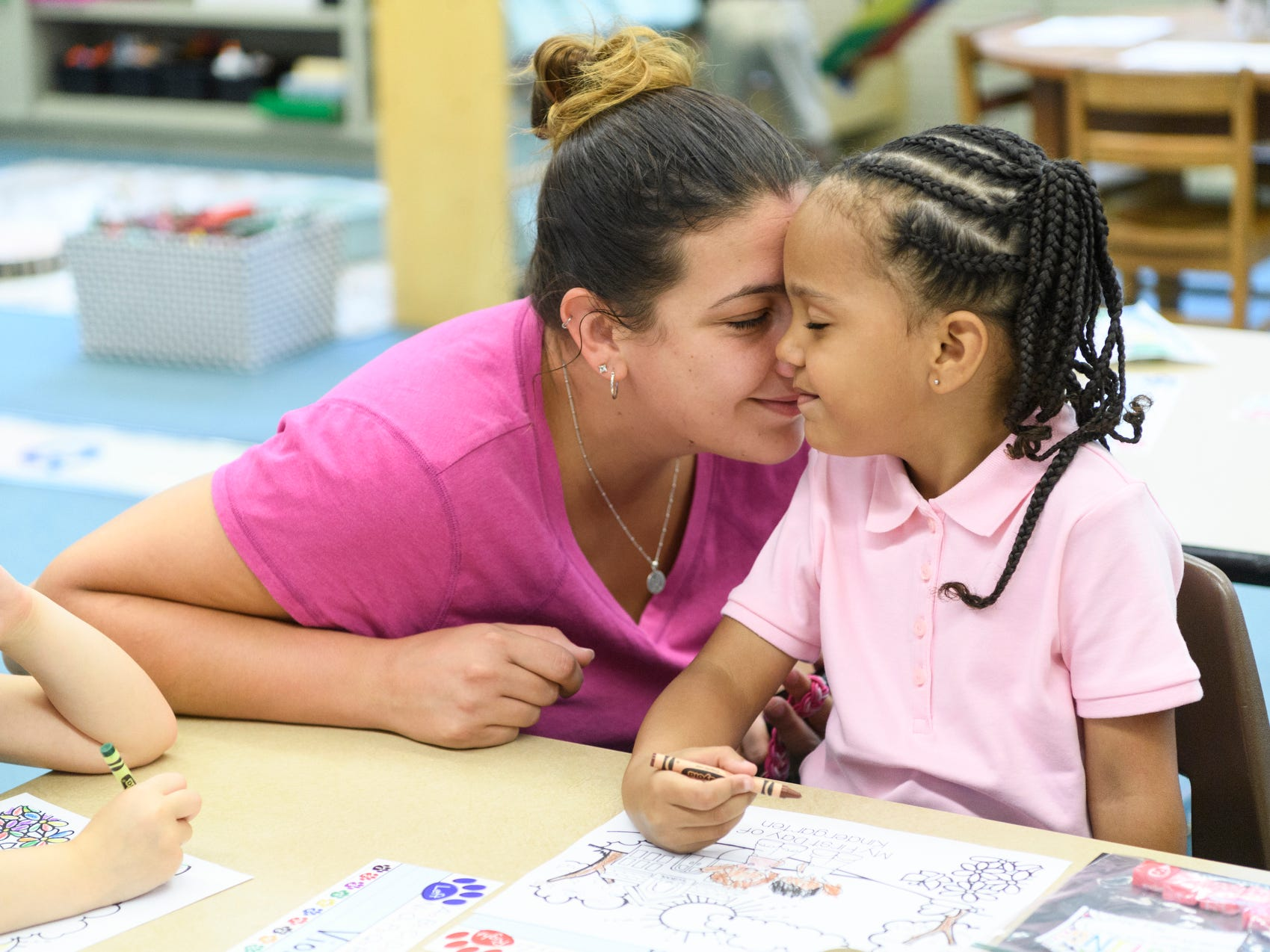 Megan French says goodbye to her five-year-old daughter Maliyah Cox inside kindergarten teacher Brooke Havill's classroom on the first day of school at Dexter Elementary School in Evansville, Ind., Wednesday, Aug. 8, 2018. Megan fought back tears as she left Maliyah working on a coloring page.