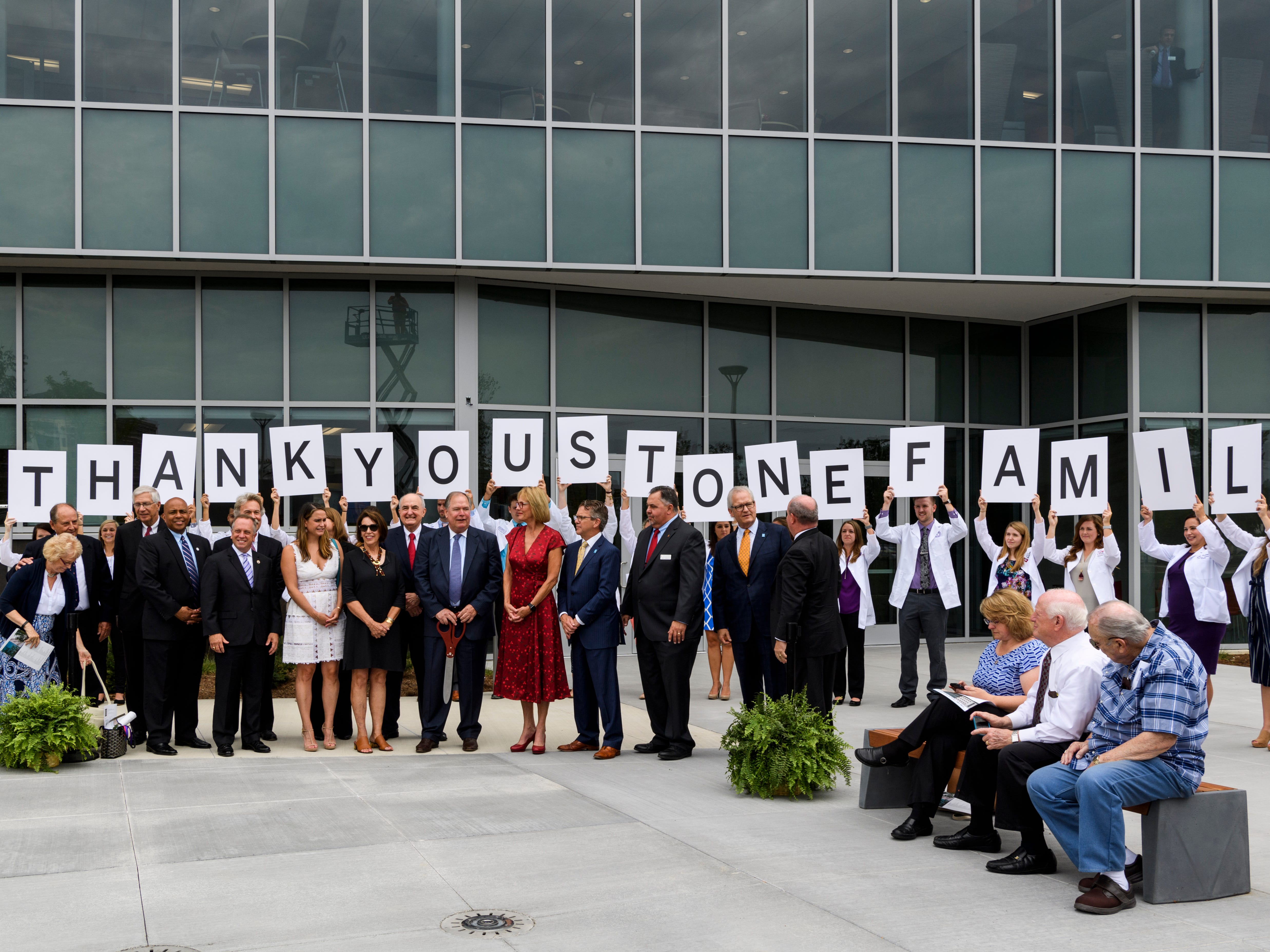 """Medical students hold up signs that say """"thank you stone family"""" during the ribbon cutting ceremony outside the new Stone Family Center for Health Sciences in Downtown Evansville, Ind., Thursday, Aug. 9, 2018. The building is named for William and Mary Stone, who made a $15 million gift to support the health sciences center."""