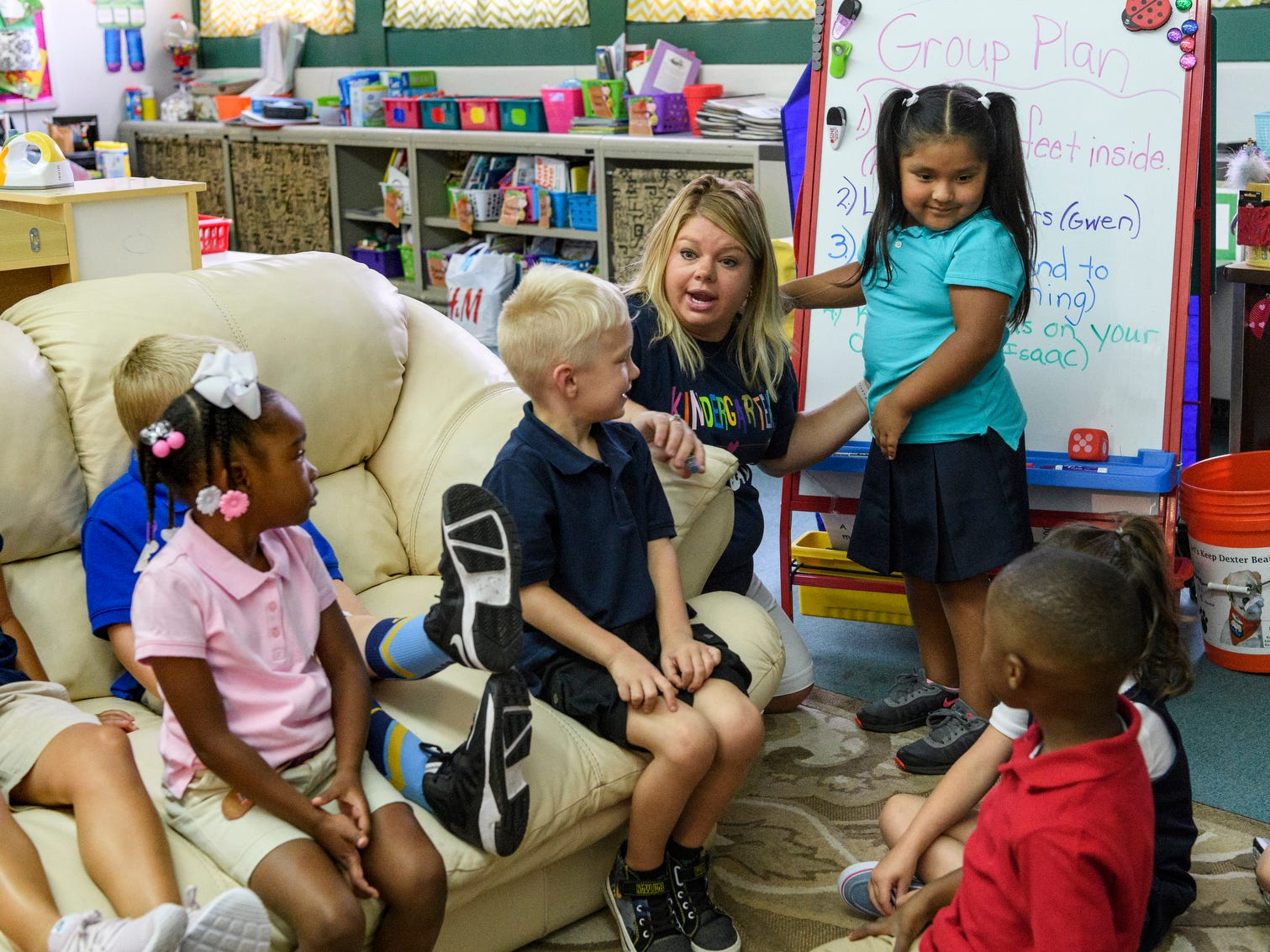 Kindergarten teacher Lyndsey Schneider, top left, talks about classroom rules with her students, including asking permission before giving a hug which she demonstrates with her student Melanie Zamora, top right, on the first day of school at Dexter Elementary School in Evansville, Ind., Wednesday, Aug. 8, 2018.