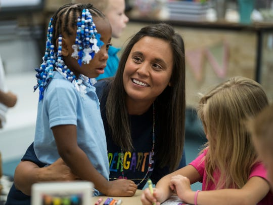 Kindergarten teacher Brooke Havill comforts Ava Crenshaw as she takes time to adjust to her new surroundings during the first day of school at Dexter Elementary School in Evansville, Ind., Wednesday, Aug. 8, 2018.