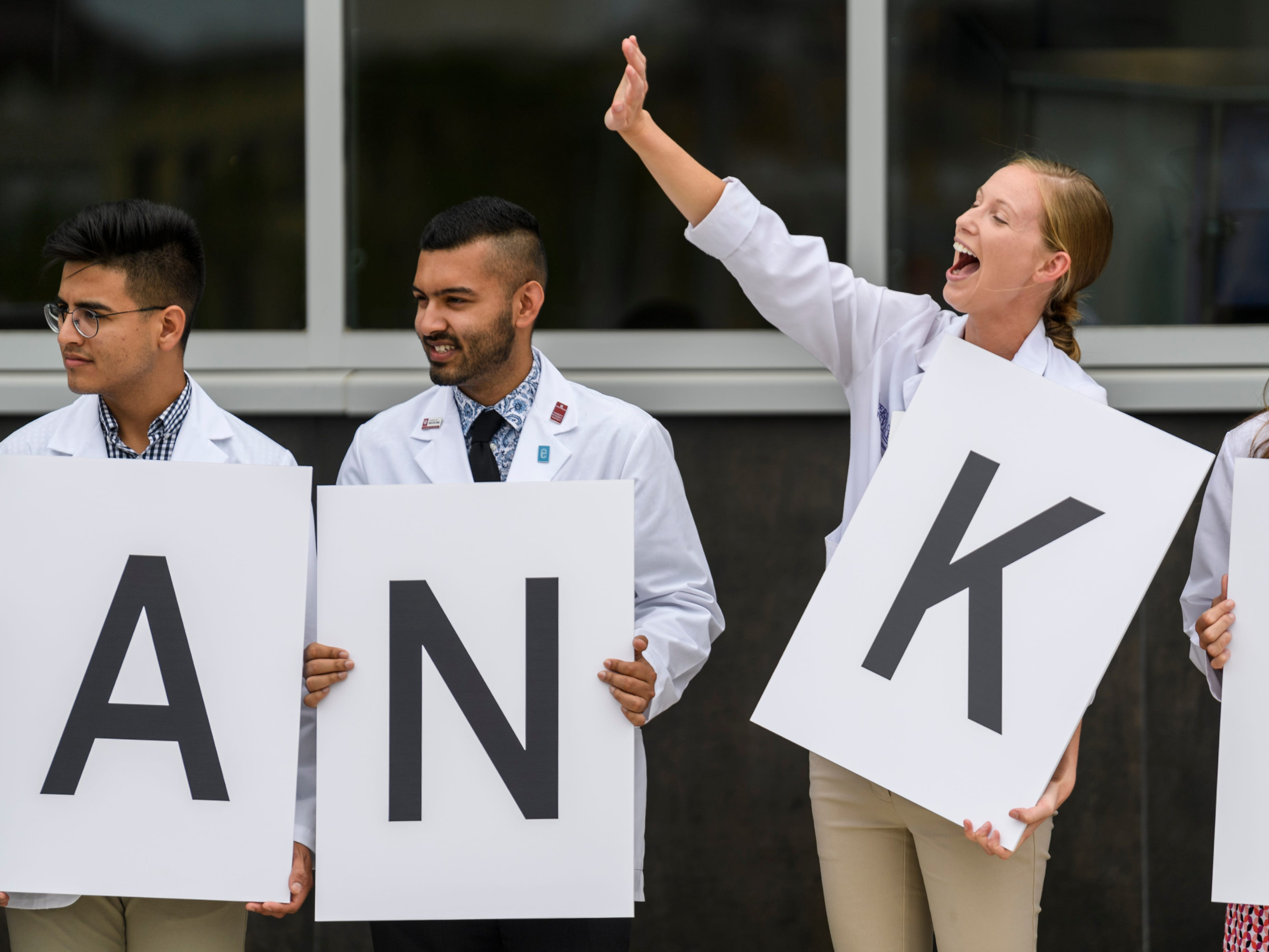 """Kelsey Hipp, second from right, a physician assistant student from the University of Evansville, waves to a friend as she and other students hold up letters that spell out """"thank you Stone family"""" during the ribbon cutting ceremony for the Stone Family Center for Health Sciences, Thursday afternoon, Aug. 9, 2018. The building is named for William and Mary Stone, who made a $15 million gift to support the health sciences center and multi-institutional partnership between Indiana University's School of Medicine, UE, the University of Southern Indiana."""