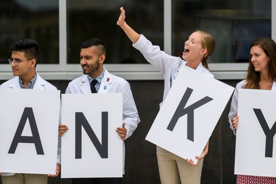 "Kelsey Hipp, second from right, a physician assistant student from the University of Evansville, waves to a friend as she and other students hold up letters that spell out ""thank you Stone family"" during the ribbon cutting ceremony for the Stone Family Center for Health Sciences, Thursday afternoon, Aug. 9, 2018. The building is named for William and Mary Stone, who made a $15 million gift to support the health sciences center and multi-institutional partnership between Indiana University's School of Medicine, UE, the University of Southern Indiana."